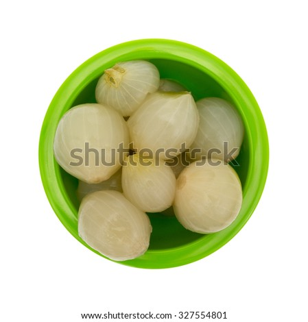 A top view of a green bowl of small whole onions on a white background.