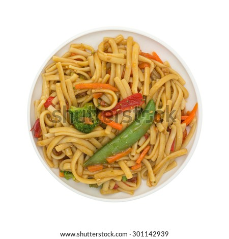 A top view of a plate of pasta, noodles and vegetables on a plate on a white background. - stock photo