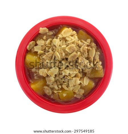 A top view of a red bowl of diced peaches in syrup topped with crunchy oats and brown sugar. - stock photo