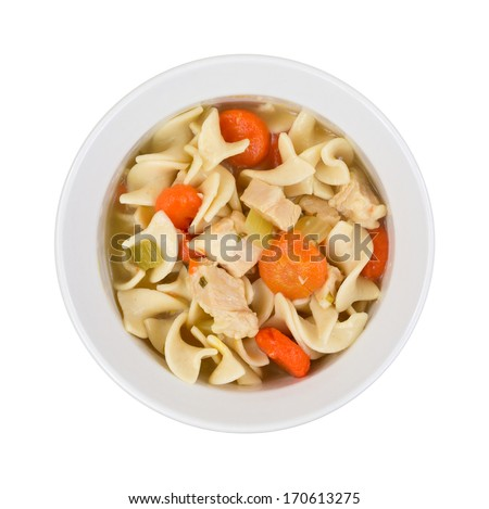 A top view of prepared noodle soup, chicken chunks, carrots in light bowl  on a white background.  - stock photo
