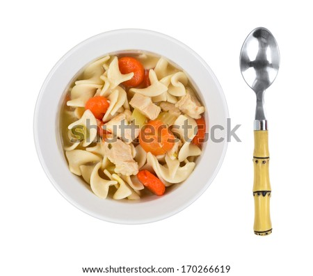 A top view of prepared noodle soup, chicken chunks, carrots in light bowl  with spoon on a white background. - stock photo