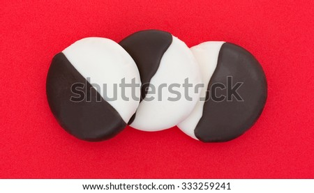A top view of three chocolate and vanilla frosted cookies in a row on a red table top. - stock photo