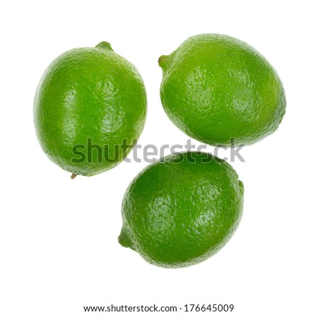A top view of three shiny limes on a white background. - stock photo
