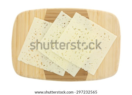 A top view of three slices of Havarti cheese on a wooden cutting board. - stock photo