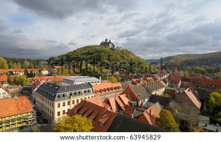 A top view over Wernigerode town with a medieval castle crowning the hill top. Wide angle picture taken from the top of a town church on a cloudy Autumn day