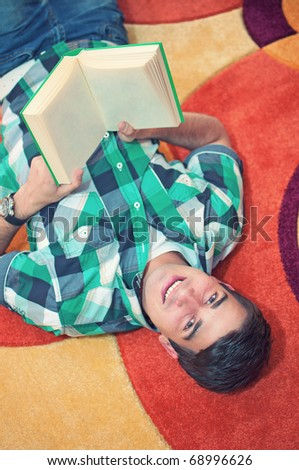 A top view portrait of young smiling attractive man holding  book lying on the carpet in living room - stock photo