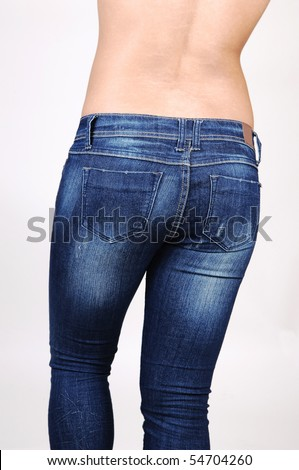 A topless Hispanic woman in jeans from the back, shooing her nice round butt, on light gray background. - stock photo
