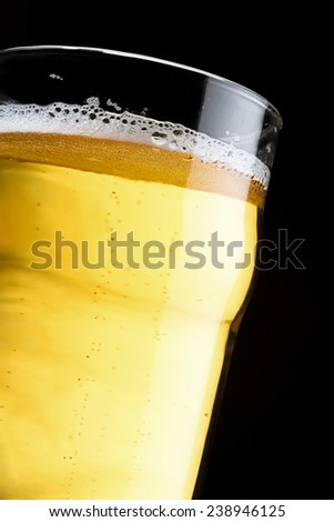A topped off beer pint over a black background