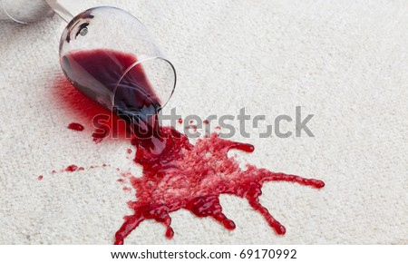 A toppled glass of red wine with a dirty carpet. - stock photo