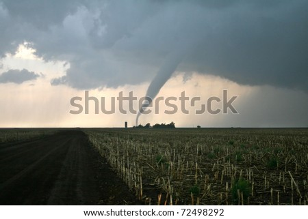 A tornado barely misses an old farm - stock photo