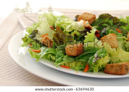 A tossed green salad with croutons on a plate - stock photo