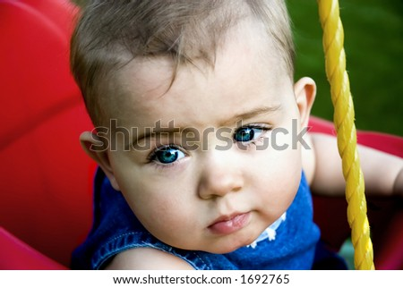 A tot sits in the swing while Mom pushes. - stock photo