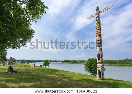 A totem pole in the park along the river - stock photo