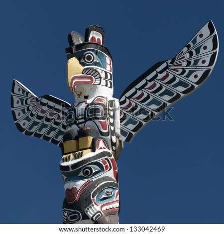 A totem wood pole in the blue background - stock photo