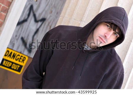 A tough looking guy posing in a grungy urban setting in a hooded sweat shirt. - stock photo