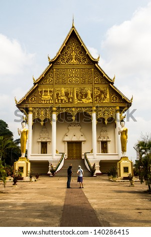 A tour guide explaining the story of Wat That Luang Neua temple - stock photo
