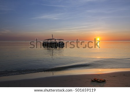 A tourist boat anchored near the shores by sunset