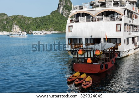 A tourist boat cruising on the waters of Ha Long Bay in Vietnam. Ha Long Bay is a UNESCO world heritage site and cruising between thousands of limestone karsts is amazing. - stock photo