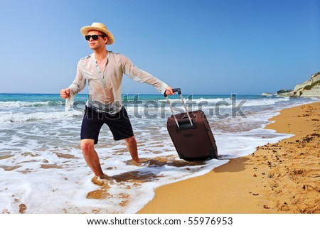 A tourist carrying a suitcase at the beach Peroulades at Corfu island, Greece