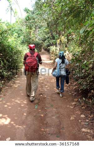 A tourist couple walking on a countryside path in the Indian tropics.