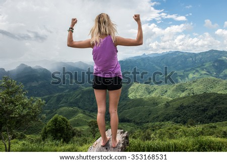 A tourist enjoying her day at the Phoukhoun mountaintop. Phoukhoun is surrounded by lush, green hills that make this place one of the most favorite tourist destinations. - stock photo