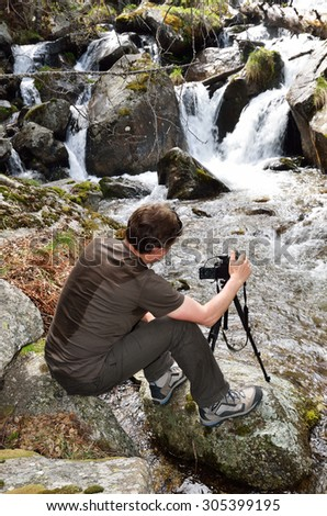 A tourist is taking photo near the small fall of the mountain stream in the spring Pyrenees.