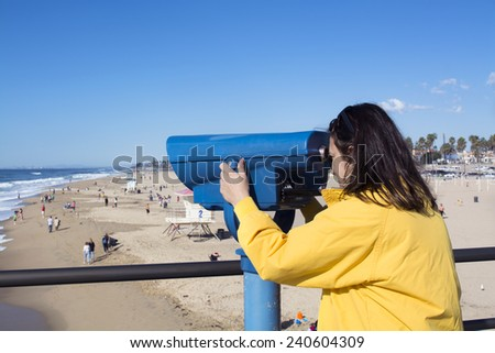 A tourist on the Huntington Beach pier watches surfers through coin operated binoculars during a bright, sunny day.