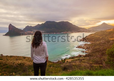 A tourist stands at a lookout point enjoying a beautiful view of Hout Bay - stock photo