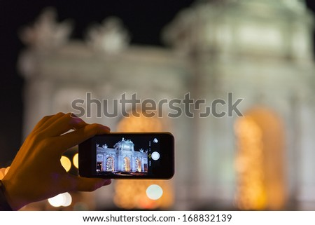A tourist takes a picture with her mobile phone of the Christmas decorations at the Puerta de Alcala in Madrid, Spain.