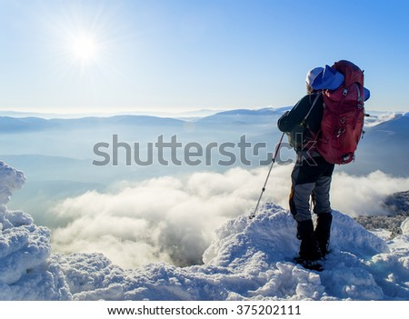 A Tourist with a backpack standing on a mountain top above the clouds and looking at the view. Direct sunlight. Clear blue sky. Winter. Mountaineering. Ukraine. Carpathians - stock photo