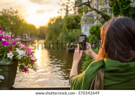 a tourist young women  in Amsterdam take pictures at a beautiful sunset on a bridge     - stock photo