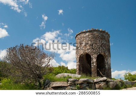 A tower, at the top of a mountain, on a clear summer day.