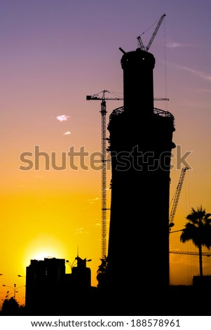 A tower in Doha, Qatar, under construction, silhouetted against the sunset. - stock photo