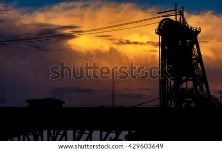 A tower of a lift bridge in Cleveland Ohio silhouetted against orange clouds at sunset - stock photo