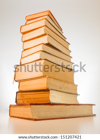 a tower of aged old books with titles out of view. wide angle capture with exaggerated perspective.