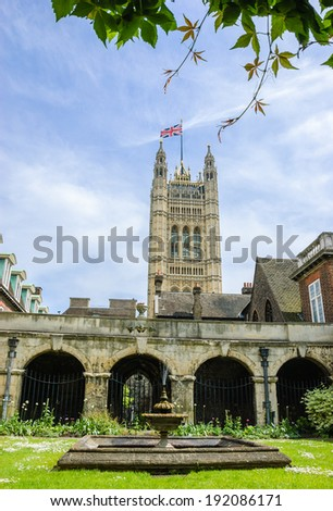 A tower of  House of Parliament with British flag seen from the courtyard of Westminster Abbey in London in a sunny day. - stock photo