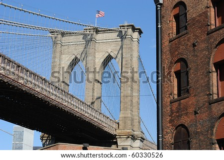 A tower of the Brooklyn Bridge in New York City over gritty brooklyn buildings. - stock photo