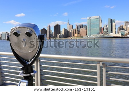 A tower viewer looking out over a body of water towards a city. - stock photo