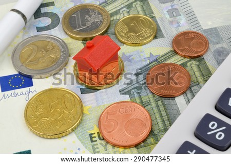 A toy house on Euro coins and notes with a calculator and pen.