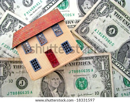 a toy house sitting on dollar bills - stock photo
