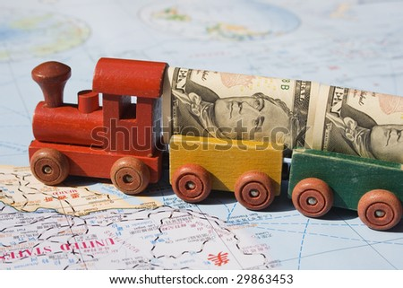 A toy train, loaded with US dollars going to North America.  The concept is trade between nations, international trade.  The map, is in English and Chinese. - stock photo