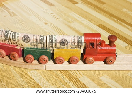 A toy train pulling a cargo of money  This picture could be a reference to 'money delivery', gravy train, cargo, freight.  Also, money supply and transferring money or wiring money. - stock photo