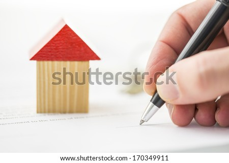 A toy wooden block building near a hand writing or holding a ballpoint pen. - stock photo
