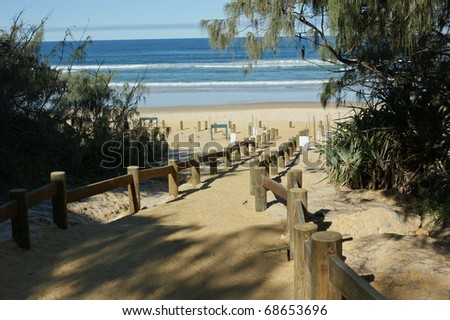 A track leads that to a sandy ocean beach - stock photo