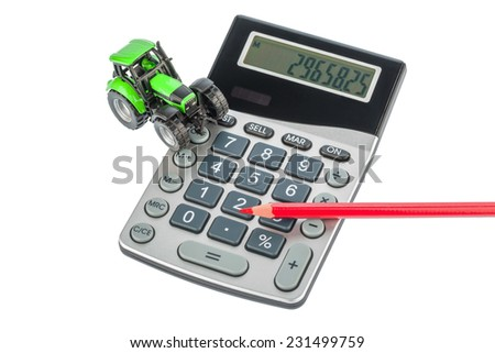 a tractor and a red pen is on a calculator. cost of gasoline, wear and insurance. costs and subsidies in agriculture - stock photo