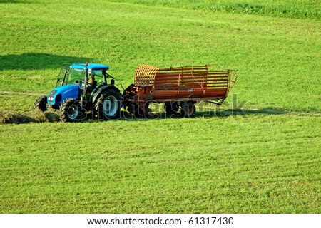A tractor collects the grass of the field to make hay