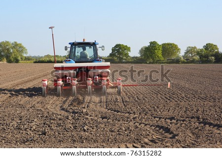 a tractor mounted seed drill in action sowing sugar beet in springtime