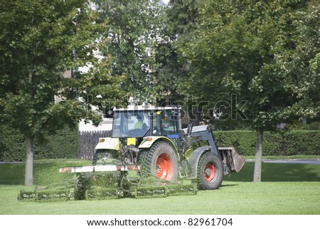 A Tractor Mowing Grass in a Park - stock photo