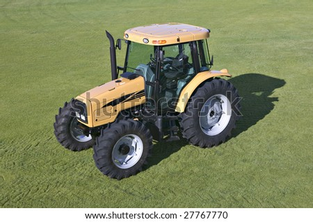 A tractor parked on green grass - stock photo