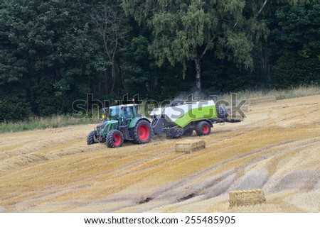 A tractor pulling a baler drives along a field of cut barley in the distance. An almost finished bale is seen in the back of the baler. - stock photo